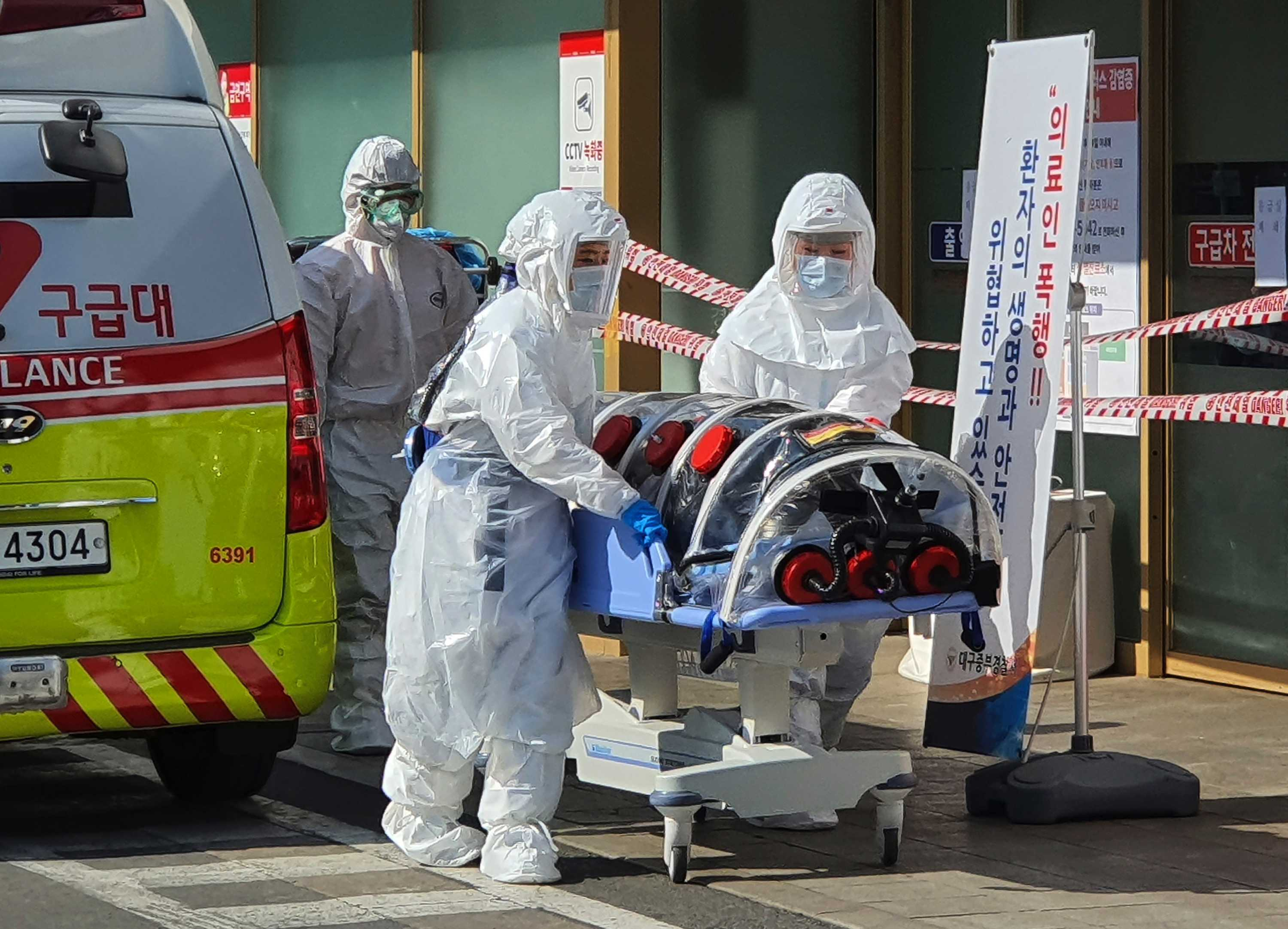 Medical workers wearing protective gear move a patient suspected of contracting the new coronavirus.