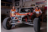 two men stand either side of a bright orange, off-road buggy. They are wearing matching bright orange shirts and black caps