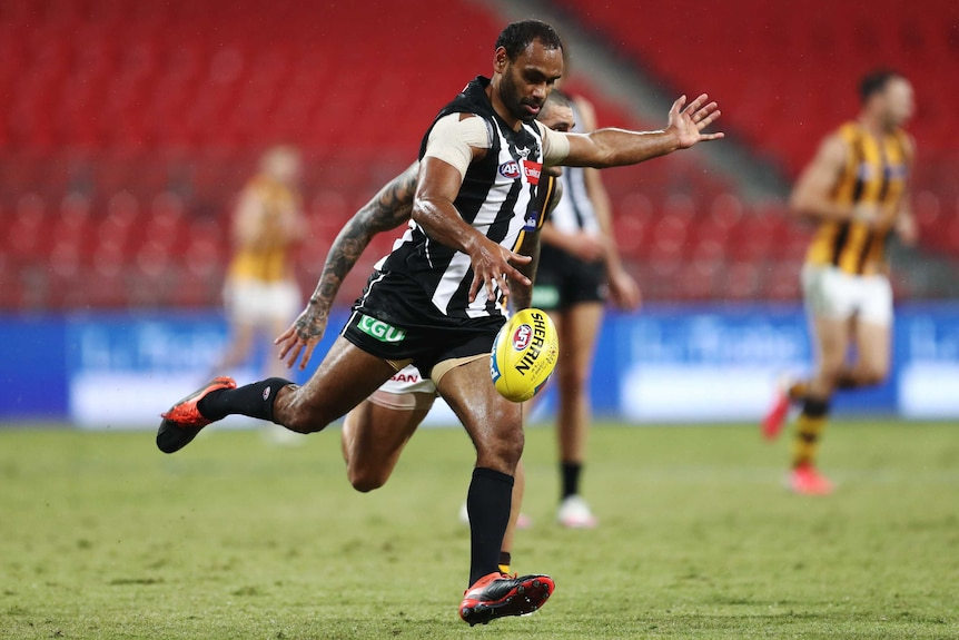 A Collingwood Magpies AFL player kicks the ball against the Hawthorn Hawks.