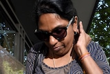 A woman wearing sunglasses walks out of the Melbourne Magistrates' Court.