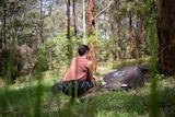 Woman kneels in front of headstone in bushland cemetery, pictured in story about eco-friendly funerals.