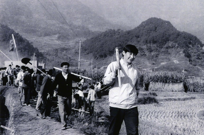 A black and white photo of Xi Jinping carrying a tool in the countryside.