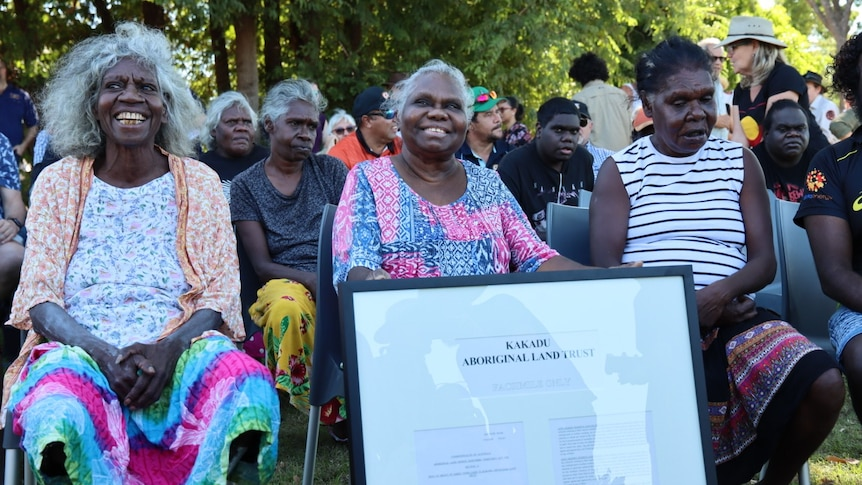 Local Mirarr people gather beneath a tree and smile in the town of Jabiru.
