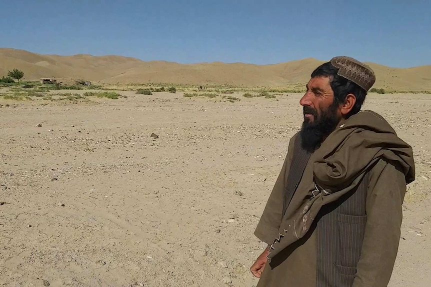 An Afghan man stands in a barren landscape talking about what hapeened.