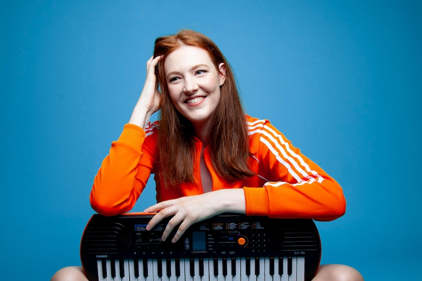 A woman sitting with a keyboard.