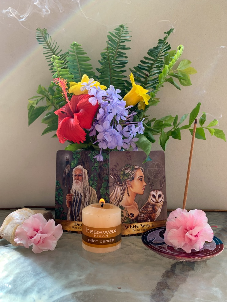 Small altar with flowers candles and incense