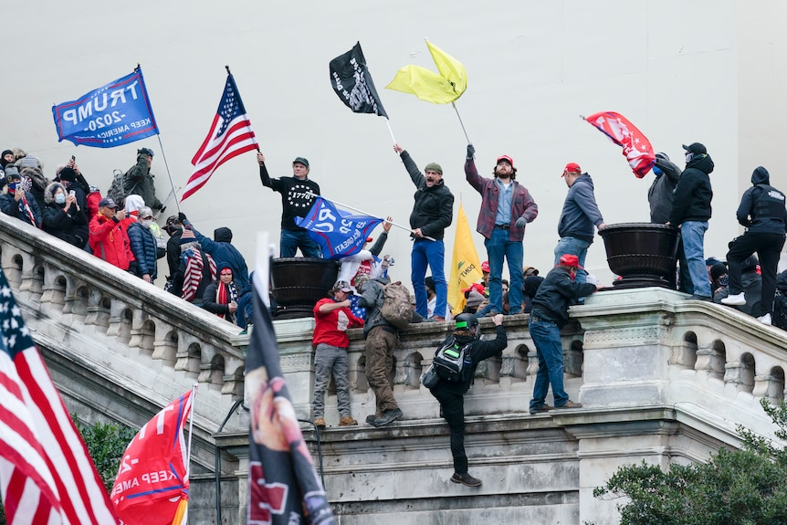 People stand on the US Capitol steps waving flags.