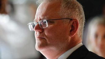 Prime Minister Scott Morrison looks to the left in portrait image. A reflection is visible in his glasses and he wears a suit.