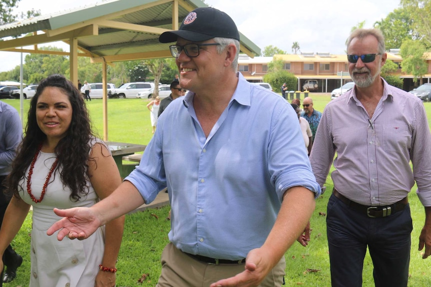 Prime Minister Scott Morrison talk with a few people on the grass in Kakadu National park