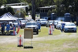 People line up in their cars at a pop-up COVID-19 testing station at Indooroopilly State High School in Brisbane