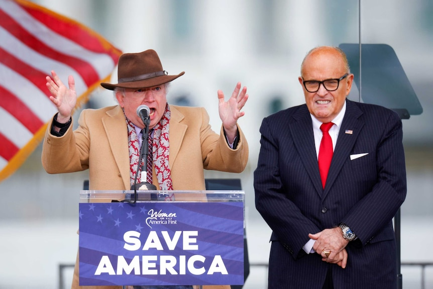 John Eastment stands behind a podium gensturing with his hands wearing a hat. Rudy Giuliani is next to him smiling