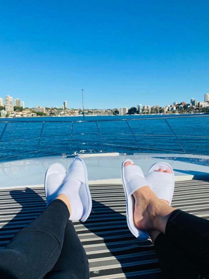 A view of two pairs of feet in slippers stretched out on a boat on Sydney Harbour.