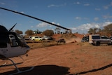 A helicopter sits on the red road, near a police car, at the scene of an accident at the Finke Desert Race.