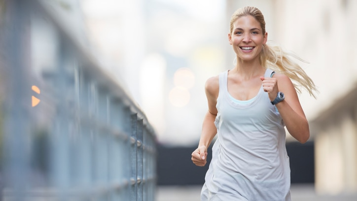A girl jogging in the city with a smile on her face