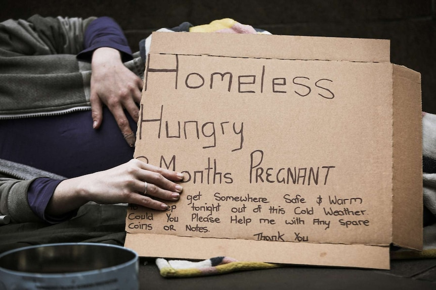 A pregnant woman lies on a footpath with a sign which says she is homeless, hungry, cold and asks for spare coins or notes.