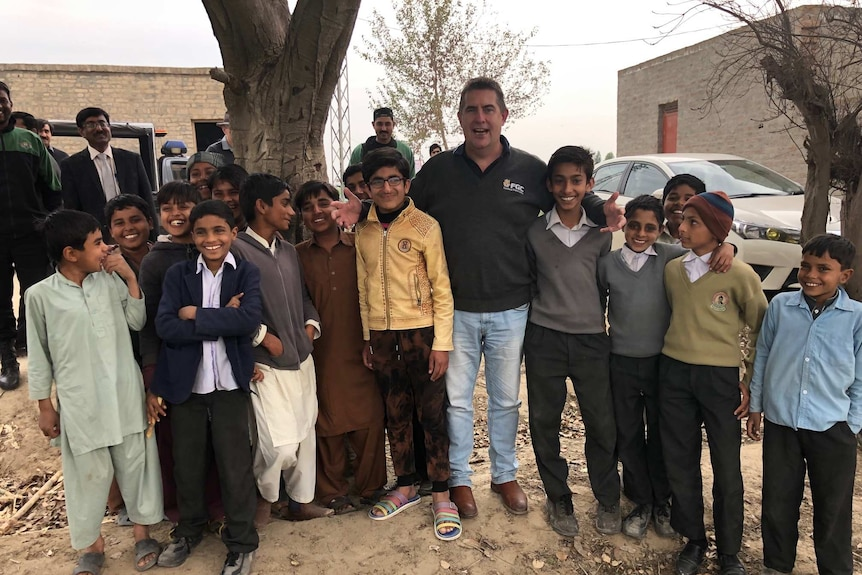 A smiling man is surrounded by a dozen children