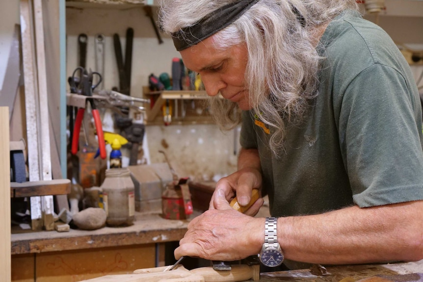 A man with long grey hair holds a tool to a piece of timber in a workshop.