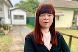 Sinead Simpkins stands outside a house and driveway, looking at the camera.