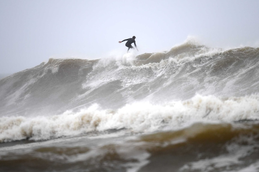A man is surfing on a large wave the sky behind him is grey