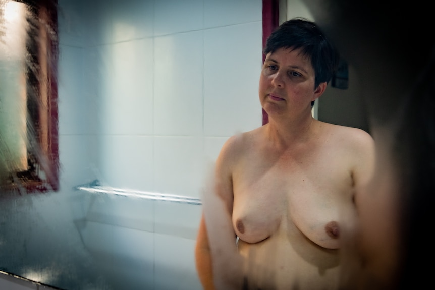 Nicola stands topless looking at her reflection in the bathroom mirror.