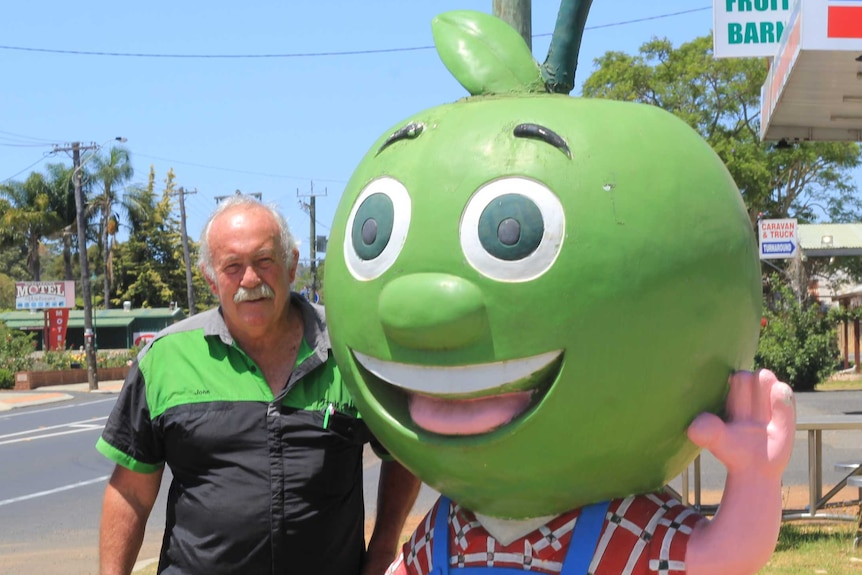 A man standing with an apple statue on a town's main street
