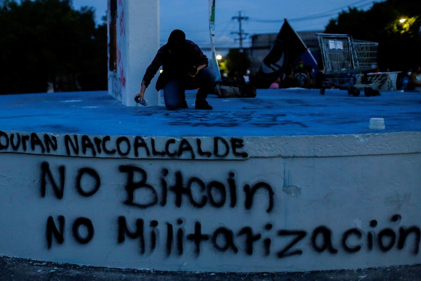 A man dressed in black takes part in a protest, spray-painting no bitcoin on a public wall at night.
