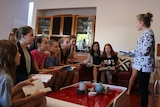 Girls sit in a lounge room discussing books