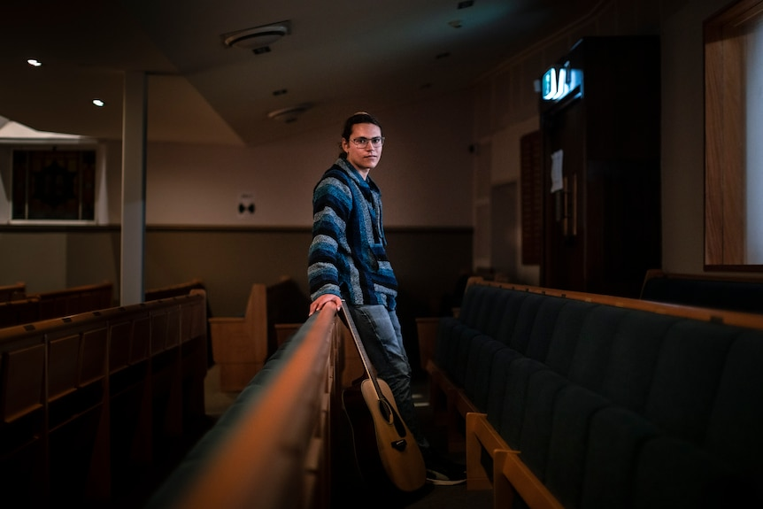 Avishai Conyer stands inside a synagogue, leaning on a bench with his guitar.