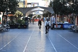 Two cyclists ride through an almost empty mall area in Bondi Junction during lockdown.