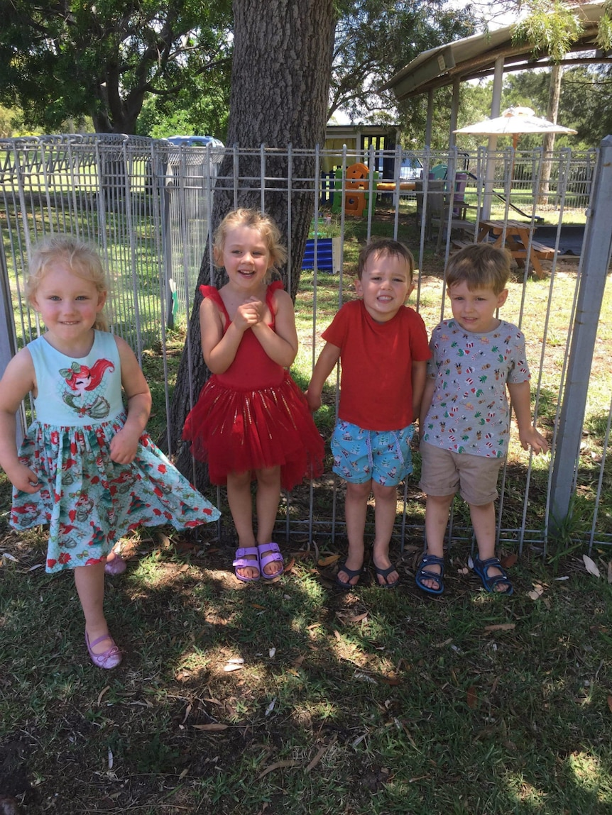 Four children pose for the camera at a playgroup near Newcastle.