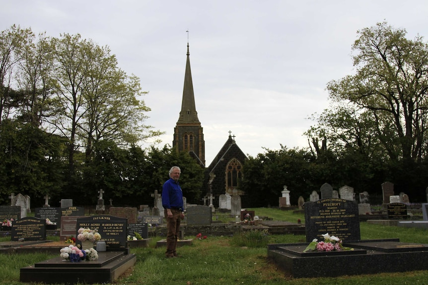 John Temple, a man with white hair and a blue shirt,  in the graveyard of the Anglican Church at Hagley, in Tasmania.