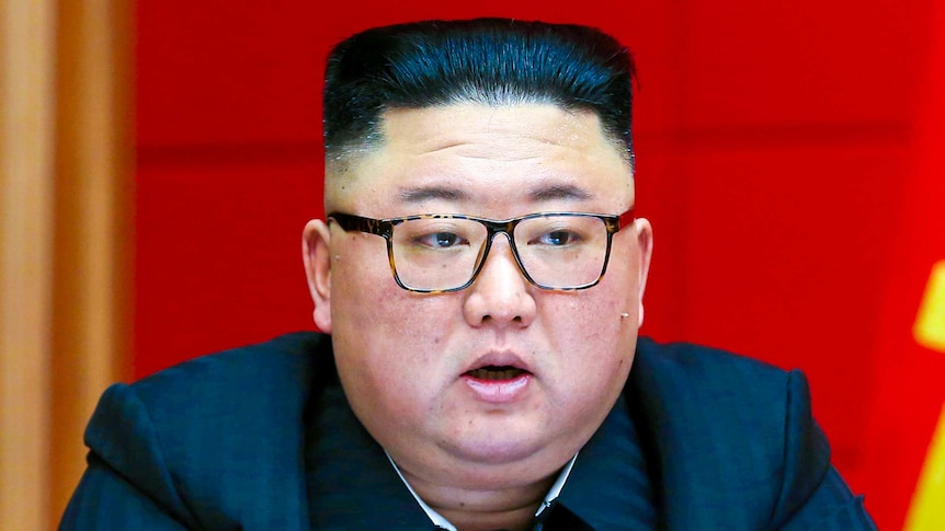 Kim Jong Un in glasses and a dark suit before a row of microphones