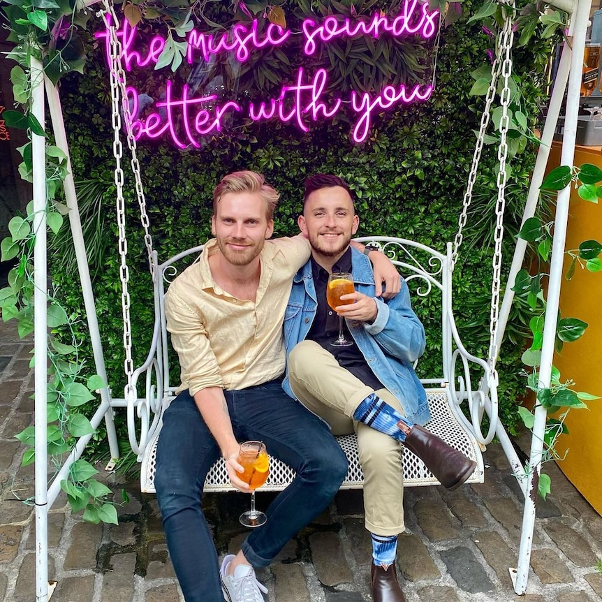 James and Tom pose arm in arm, holding cocktails, under a sign that reads 'the music sounds better with you.'