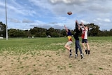 Three young boys try to mark a football.