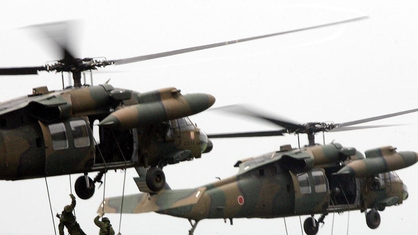 Japanese soldiers rappel from helicopters