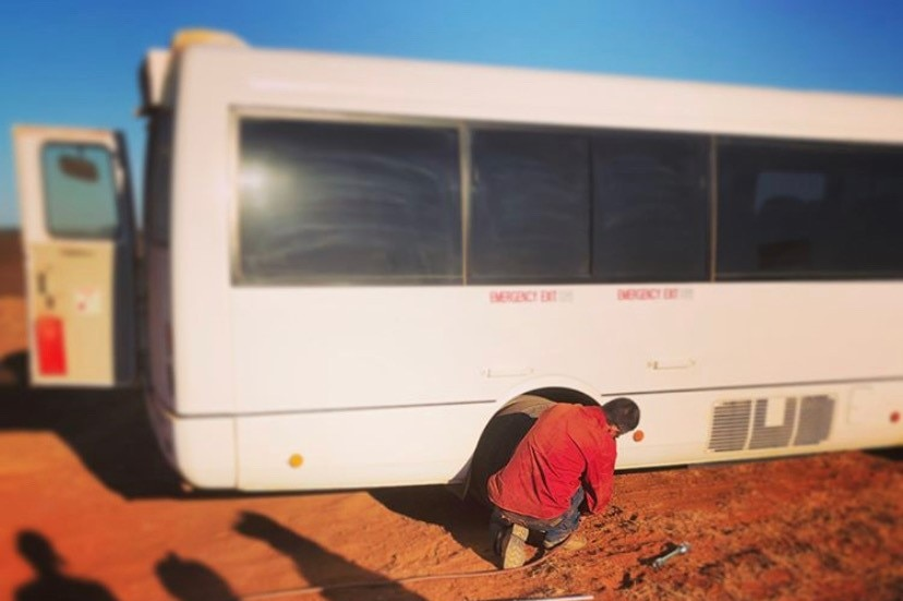 a white school bus stands on a red dirt road while a person changes its tyre