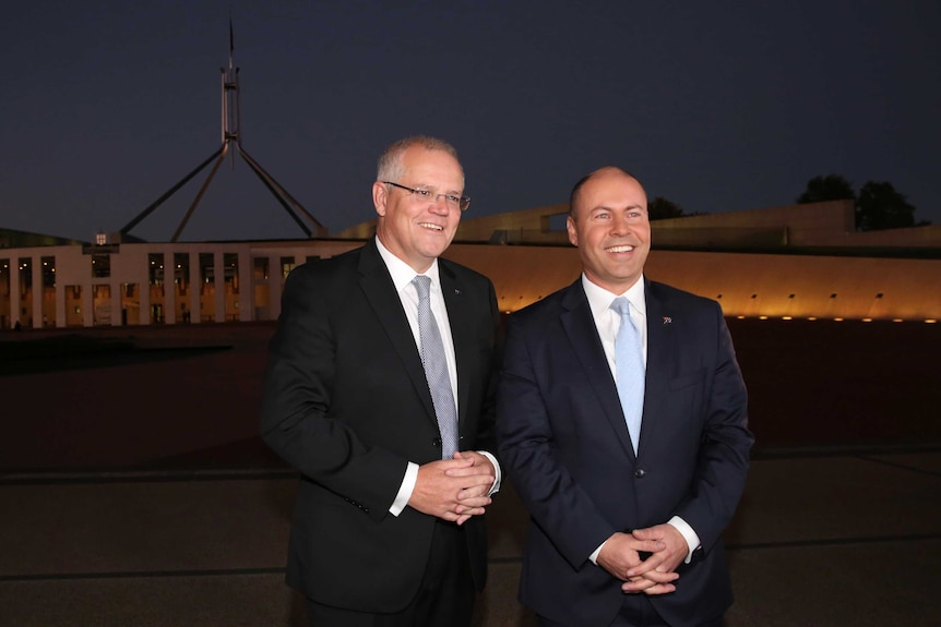 Wearing suits and smiling, Scott Morrison and Josh Frydenberg stand outside Parliament House before dawn.