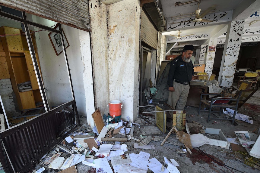 The site of a suicide bomb attack at a district court in Mardan. Walls are knocked down, paper everywhere, blood splatters.