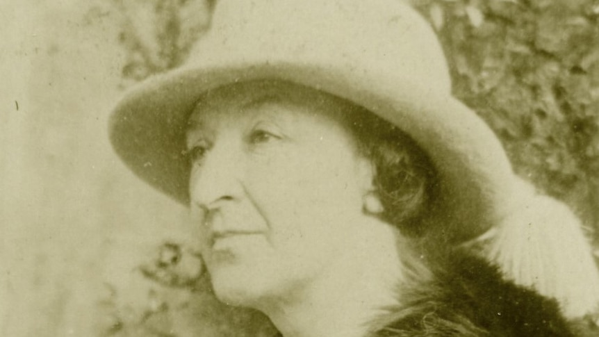 Woman with fur coat and a hat stares into the distance while sitting down.