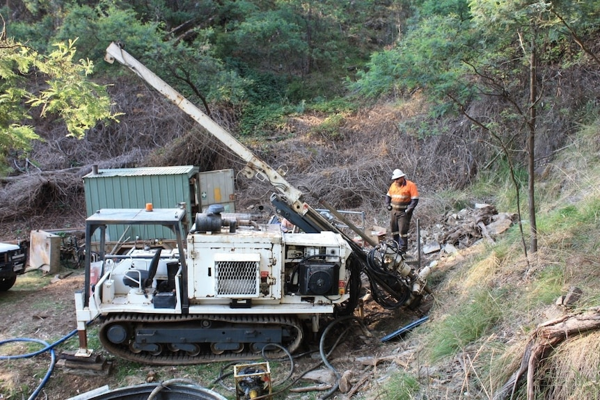A man in a bright orange shirt looks at a machine that is drilling into the earth.