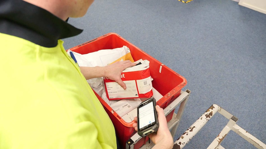 An Australian Post worker scans the code on a package.