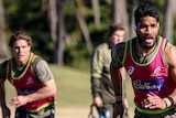 Sitaleki Timani runs at Wallabies training with Michael Hooper in the background.