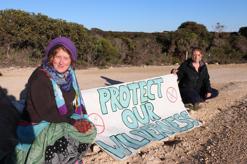"""Two women sit in the sand holding a sign between them that reads """"protect our wilderness"""""""