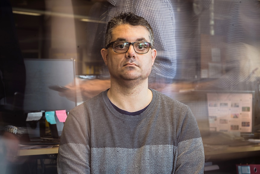 A man with glasses and a grey jumper sits in an office surrounded by blurred figures of office workers.