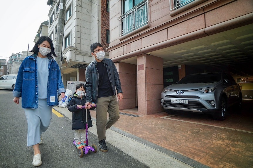 A Korean couple in face masks walk next to a small boy on a razor scooter