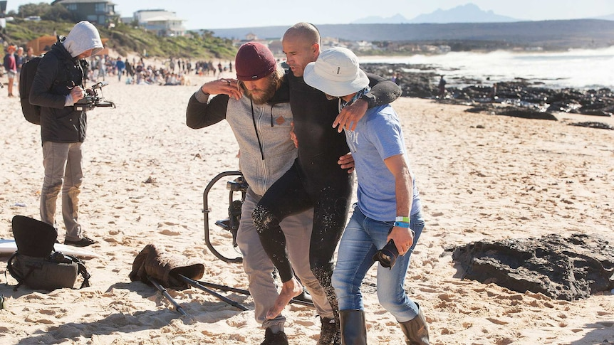 Kelly Slater was helped up the beach after breaking his foot while surfing at Jeffreys Bay.