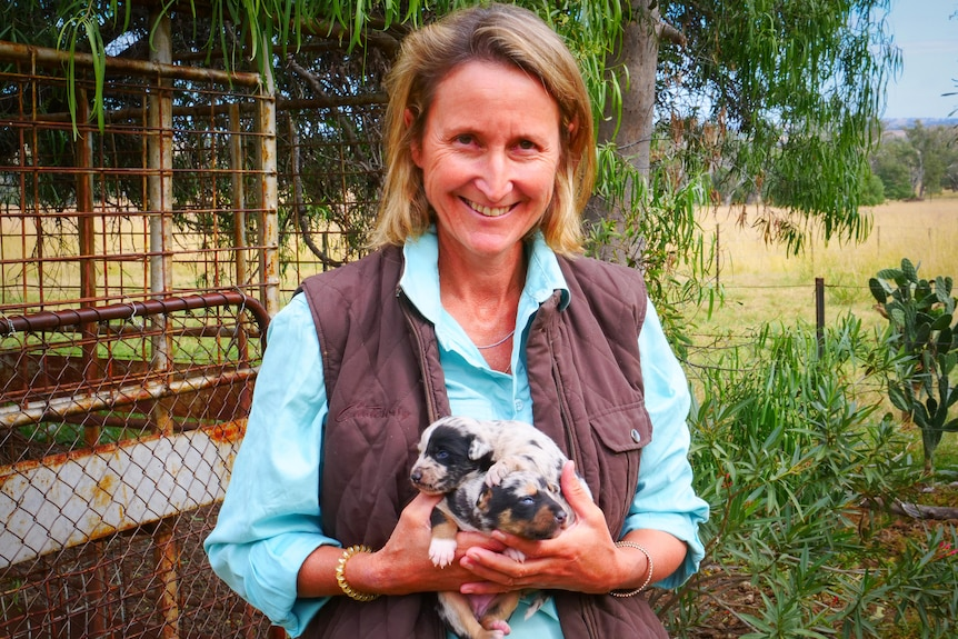 A woman stands in a shirt and vest holding to small puppies.