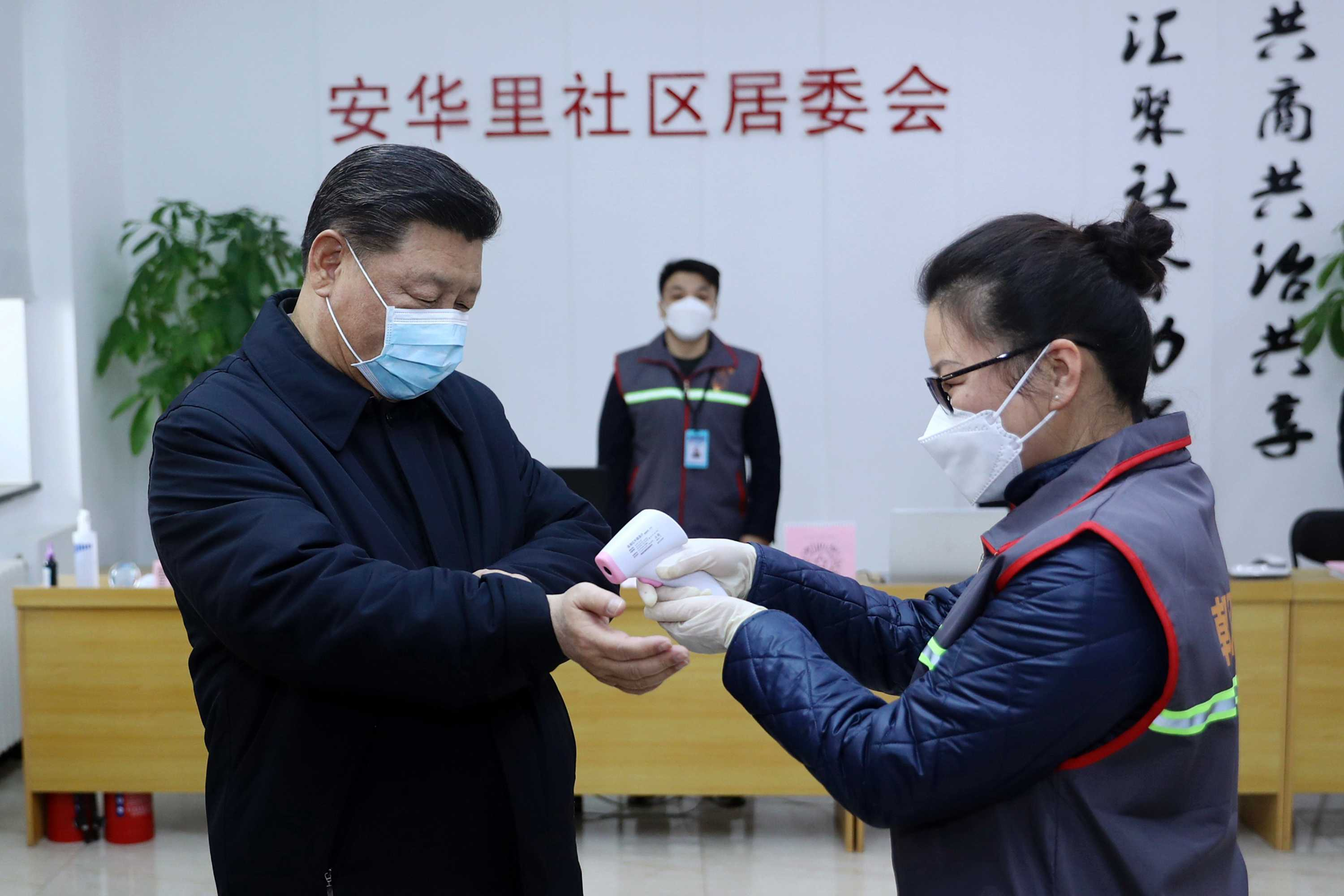Xi Jinping wearing a face mask and getting his temperature checked as he visits  community health centre in Beijing.