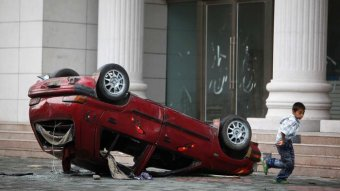 Photo shows a damaged, overturned red car with a child running alongside.