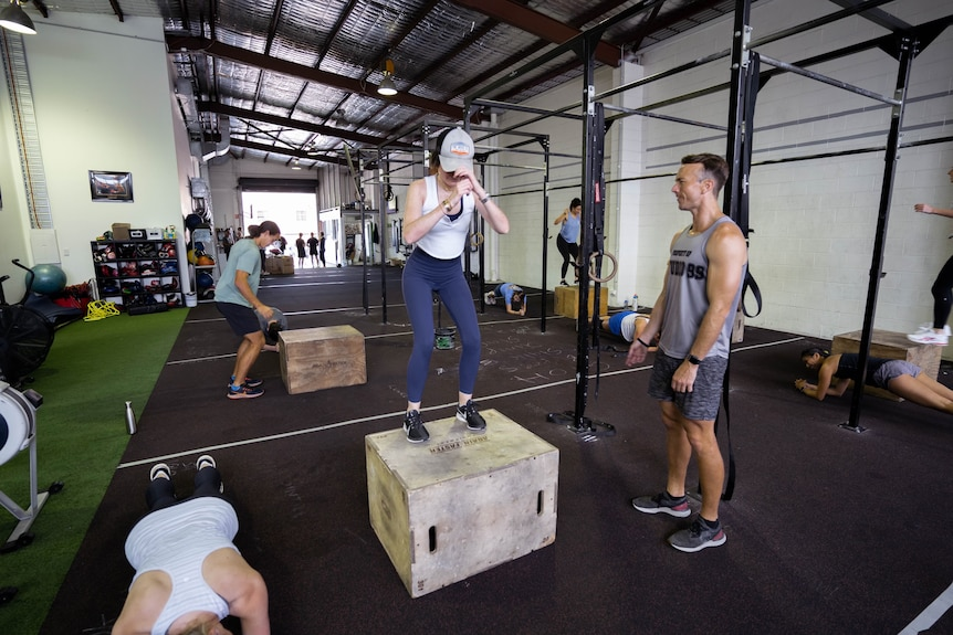 Tim supervises a client doing box jumps as others perform other exercises in the background